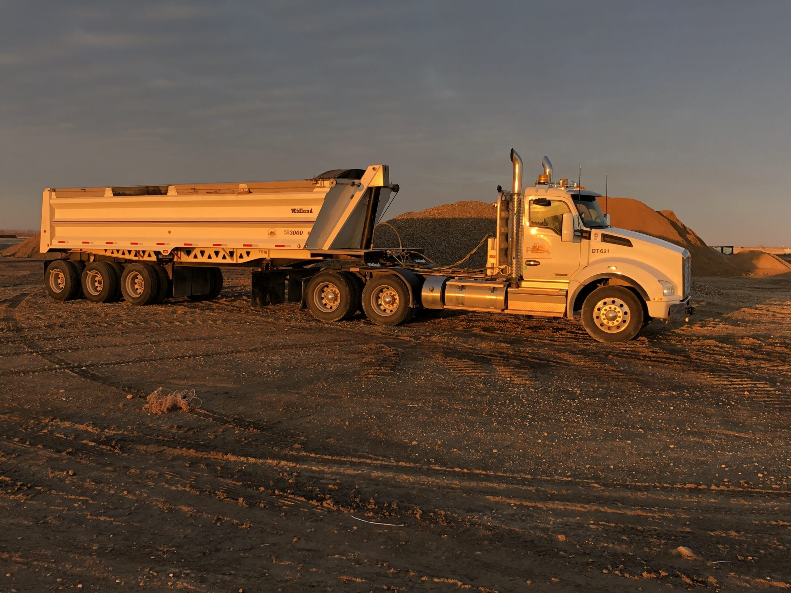Semi-truck at dusk pulling a load of gravel to the landfill.